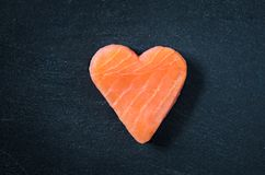 Salmon fillet copy space black slate background, healthy eating omega 3 concept. Heart shaped salmon steak top view on slate stock images