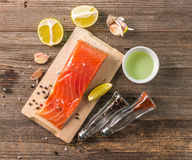 Salmon fillet, cut lemon on board, topview Royalty Free Stock Images