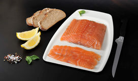 Salmon fillet cut into slices. Fillet knife, bread, lemon and spices on a black background Stock Photo