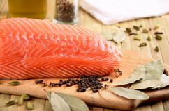 Salmon fillet on a cutting board close-up. Spices and a bottle of olive oil on the table. horizontal Royalty Free Stock Photo