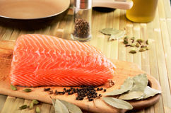Salmon fillet on a cutting board on the table. On the table cookware and spices. horizontal Stock Photos