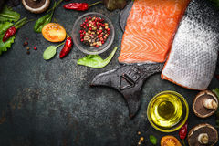Salmon fillet with delicious ingredients for cooking on dark rustic wooden background, top view, frame. Stock Image