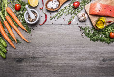 Salmon fillet with delicious ingredients for cooking a variety of vegetables and herbs, salt in the wooden spoon, cherry tomatoes, royalty free stock photography