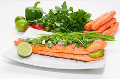 Salmon fillet diet food. Grilled salmon diet fish food salad with tomato, bell pepper and carrot vegetables in background Stock Image