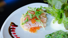 Salmon fillet and eggs with sauce. On plate Royalty Free Stock Image