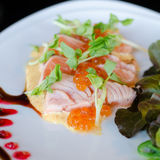 Salmon fillet and eggs with sauce. On plate Stock Photo