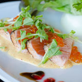 Salmon fillet and eggs with sauce. On white plate Royalty Free Stock Image