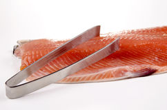 Salmon fillet and a fish bone tong Stock Image