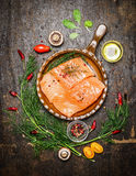 Salmon fillet in fried pan with herbs and ingredients for cooking on rustic wooden background, top view. Royalty Free Stock Photography