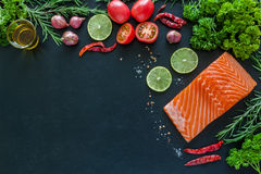 Salmon fillet with garnish on blackboard ready to cook Stock Image