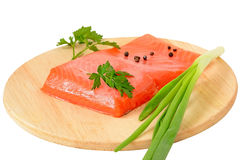 Salmon fillet, green onion and parsley on kitchen board Stock Photos