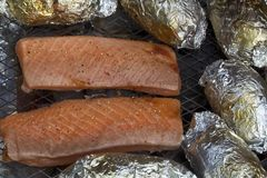 Salmon fillet on grill. Salmon fillets and potatoes on an outdoor grill Stock Photos