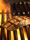 Salmon fillet on the grill with flames Royalty Free Stock Image