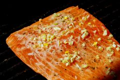 Salmon fillet on the grill with flames closeup. On barbecue grill, close up royalty free stock images