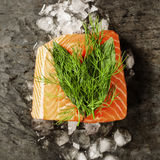 Salmon Fillet on Ice. Raw salmon fillet and ingredients for cooking in a rustic style. Top view Stock Photo