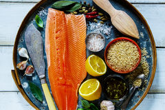 Salmon fillet and ingredients. Salmon fillet and brown rice on old rusty iron background with fresh ingredients for tasty cooking over rustic wooden table, top Royalty Free Stock Images