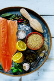 Salmon fillet and ingredients. Fresh salmon fillet and brown rice on old rusty iron background with ingredients for tasty cooking over rustic wooden table, top Stock Photos
