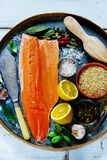 Salmon fillet and ingredients. Raw salmon fillet and brown rice on old rusty iron background with fresh ingredients for tasty cooking over rustic wooden table Royalty Free Stock Images