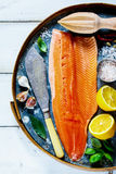 Salmon fillet and ingredients. Top view of salmon fillet on old rusty iron background with fresh ingredients for tasty cooking  over rustic wooden table. Healthy Stock Photos