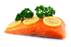 Salmon fillet with lemon and parsley. Raw salmon fillet with parsley and lemon on white background Royalty Free Stock Photo