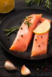 Salmon fillet with lemon and rosemary, garlic and pepper on black plate on dark wooden background. stock images