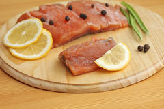 Salmon fillet with lemon and spices on wooden board Stock Photography