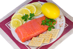Salmon fillet and lemons on a platter on a white background. Royalty Free Stock Photography