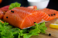 Salmon fillet with lettuce, lemon and black pepper Stock Photos