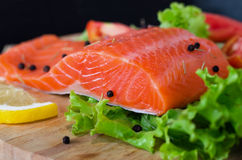 Salmon fillet with lettuce, lemon and black pepper Royalty Free Stock Photo