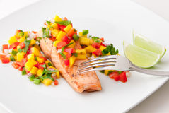 Salmon fillet with mango salsa on white plate. Royalty Free Stock Photos