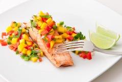 Salmon fillet with mango salsa on white plate. Royalty Free Stock Photos