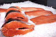 Salmon fillet next to steaks on ice royalty free stock image