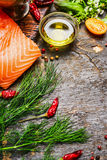 Salmon fillet with oil and fresh hebrs and seasoning for cooking on rustic wooden background Stock Image