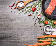 Salmon fillet in a pan with herbs, vegetables and spices place for text,frame wooden rustic background top view. Salmon fillet in a pan with herbs, vegetables Stock Images