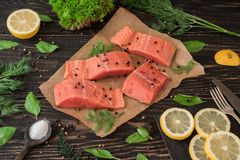 Salmon fillet on parchment paper. Salmon fillet on rustic kitchen table with fresh ingredients for tasty cooking and frying pan. Wooden background, frame Royalty Free Stock Photography
