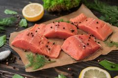 Salmon fillet on parchment paper. Salmon fillet on rustic kitchen table with fresh ingredients for tasty cooking and frying pan. Wooden background, frame Stock Photo