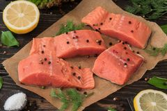 Salmon fillet on parchment paper. Salmon fillet on rustic kitchen table with fresh ingredients for tasty cooking and frying pan. Wooden background, frame Stock Photography