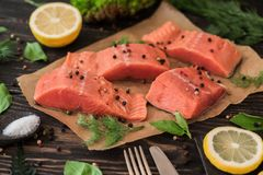 Salmon fillet on parchment paper. Salmon fillet on rustic kitchen table with fresh ingredients for tasty cooking and frying pan. Wooden background, frame Stock Image