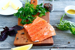 Salmon fillet with parsley, basil and lemon on a cutting board Stock Photography