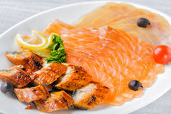Salmon fillet pieces, conger eel, sturgeon pieces served with lemon, black olives, herbs and cherry tomato on white plate close up Royalty Free Stock Photos