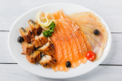 Salmon fillet pieces, conger eel, sturgeon pieces served with lemon, black olives, herbs and cherry tomato on white plate and wood Stock Images