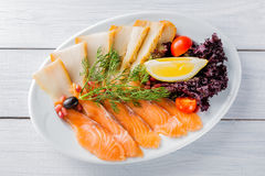 Salmon fillet pieces, sturgeon pieces served with lemon, black olives, herbs, cherry tomato and pomegranate seeds on white plate a Royalty Free Stock Images