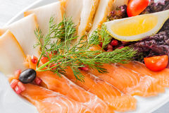 Salmon fillet pieces, sturgeon pieces served with lemon, black olives, herbs, cherry tomato and pomegranate seeds on white plate c. Lose up with selective focus Stock Image