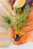 Salmon fillet pieces, sturgeon pieces served with lemon, black olives, herbs, cherry tomato and pomegranate seeds on white plate c. Lose up with selective focus Stock Photos