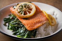 Salmon fillet with rice and spinach garnish. Fish steak. Lemon salmon on white plate on wooden background. Horizontal royalty free stock photography
