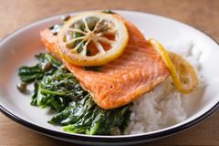 Salmon fillet with rice, spinach and lemon. Salmon with garnish. Fish for healthy dinner. Salmon fillet with rice, spinach and lemon. Salmon with garnish. Fish Stock Photography