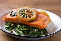 Salmon fillet with rice, spinach and lemon. Salmon with garnish. Fish for healthy dinner. Salmon fillet with rice, spinach and lemon. Salmon with garnish. Fish Royalty Free Stock Photo
