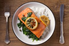 Salmon fillet with rice, spinach and lemon. Salmon with garnish. Fish for healthy dinner. View from above, top Royalty Free Stock Photography