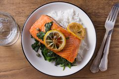 Salmon fillet with rice, spinach and lemon. Salmon with garnish. Fish for healthy dinner. View from above, top Stock Images