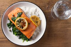 Salmon fillet with rice, spinach and lemon. Salmon with garnish. Fish for healthy dinner. View from above, top Royalty Free Stock Images